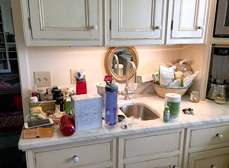Before the KonMari Method, my marble kitchen counter is covered in knickknacks, vitamin bottles, 2 different waterbottles, and other clutter.